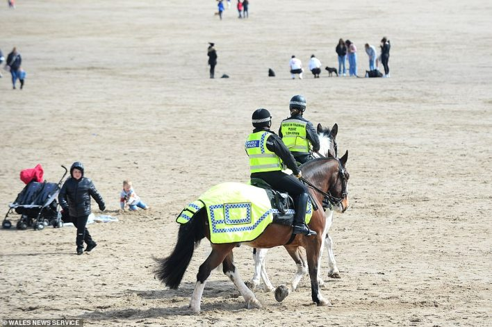 Police officers patrolled the shore on horseback in Barry Island (pictured), weaving between punters on the sand while ensuring social distancing rules were being maintained