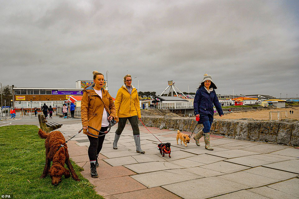 Three women are seen walking their dogs inPorthcawl, Wales, on Sunday. Under Wales's new rules, six people from two different households can meet up outside
