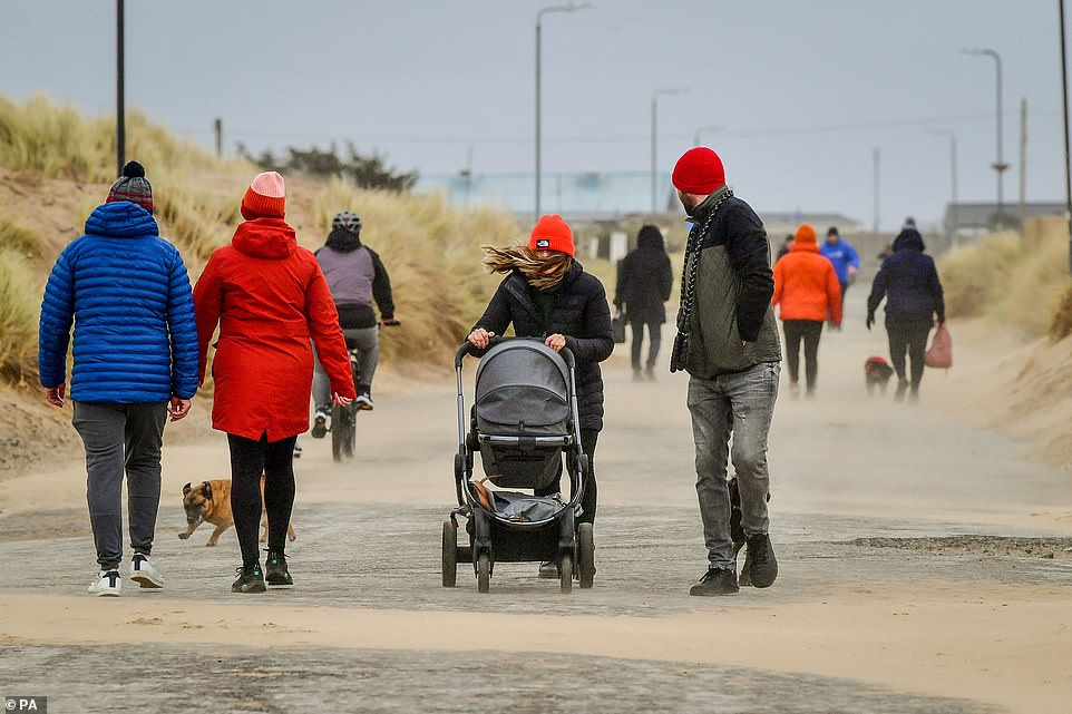 Meanwhile, defiant locals took to the sand in Porthcawl despite strong winds. Pictured: Walkers are seen battling through heavy wind