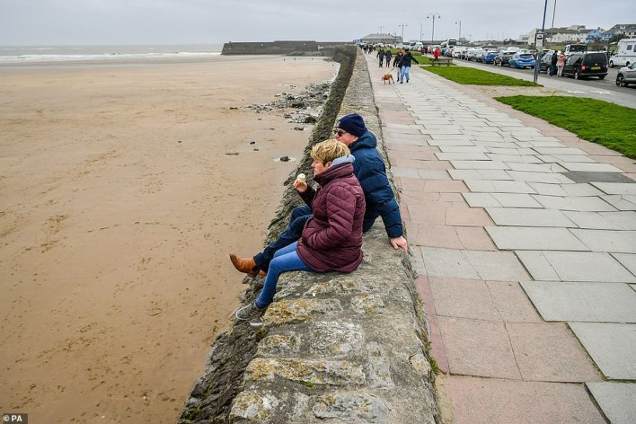 Two people are seen watching the sea in Porthcawl, Wales, on the first Sunday since lockdown measures were partially lifted in Wales