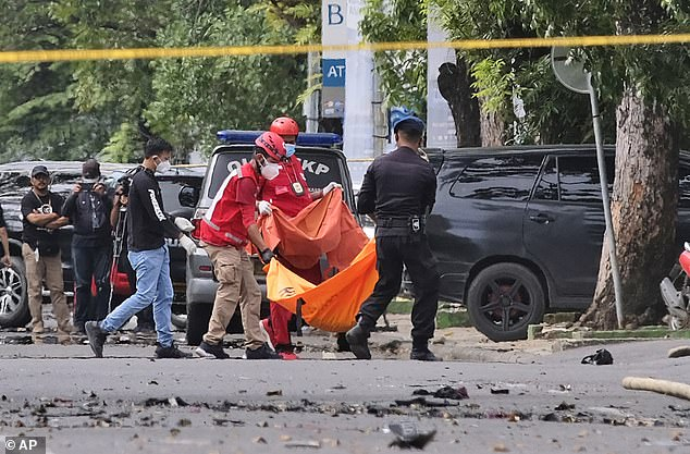 Two suicide bombers were killed after they blew themselves up outside a Roman Catholic Church on Sunday. Pictured are police officers and rescue workers carrying a body bag from the scene of the blast in South Sulawesi, Indonesia