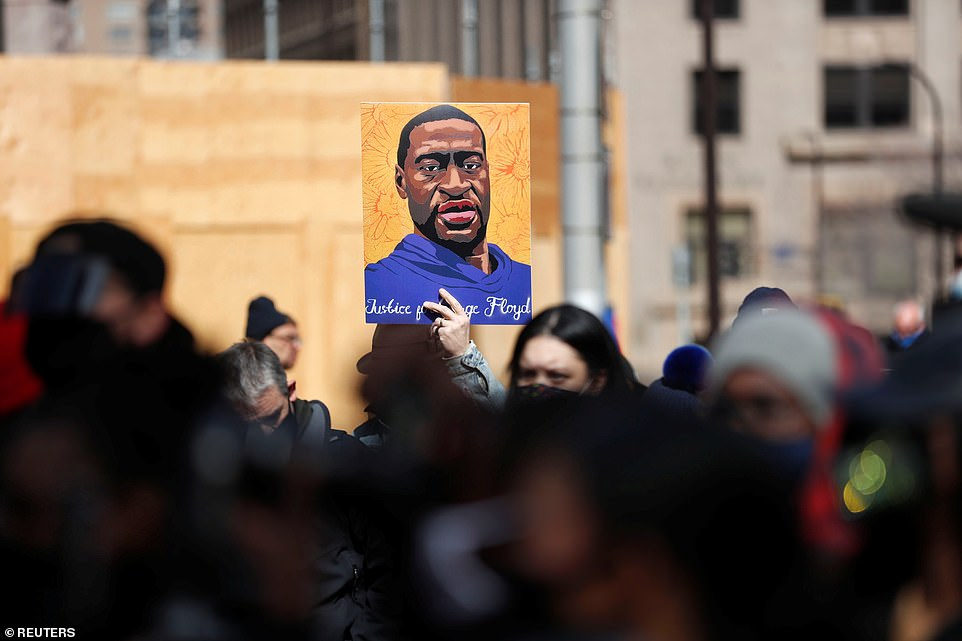 Demonstrators wave a portrait of Floyd during protests in Minneapolis on Sunday