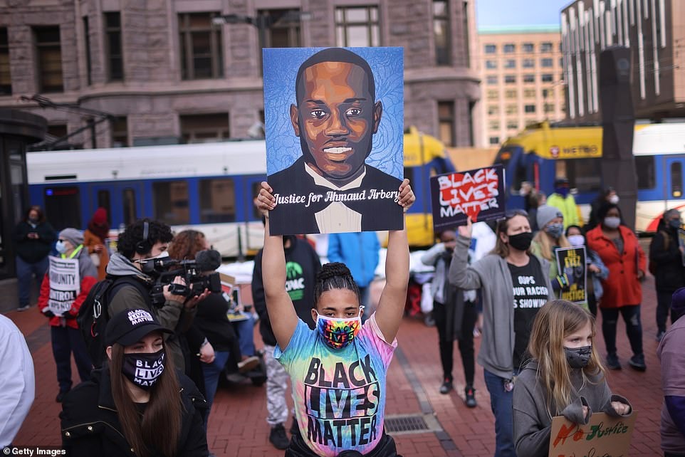 A Black Lives Matter supporter holds up a portrait of Ahmaud Arbery, a black man who was fatally shot by two white men in Georgia last year