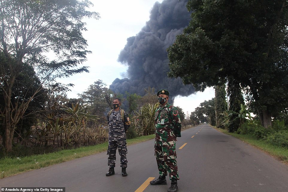 Pictured: Indonesian military personnel stand guard along a road near to the Pertamina oil refinery in Balongan this morning as emergency services continue to tackle the blaze