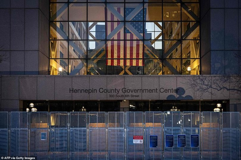 A fence is seen erected around the Hennepin County Government Center before opening statements on Monday