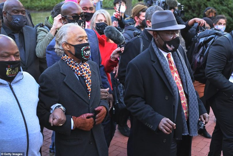 Rev. Al Sharpton, second left, and civil rights attorney Ben Crump, right, escort family members of George Floyd into the Hennepin County Government Center on Monday
