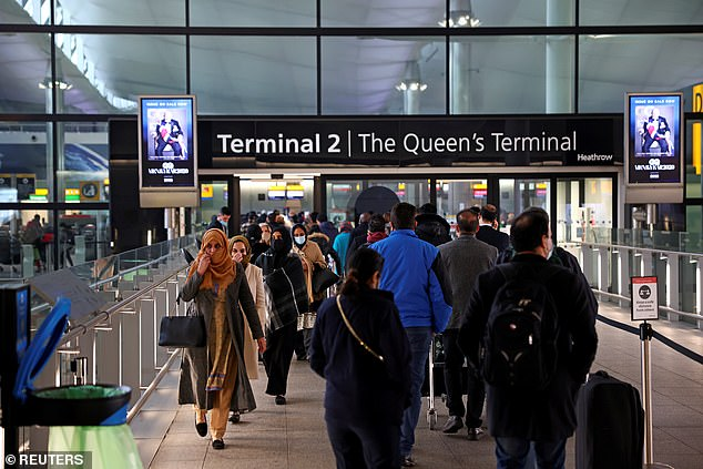 People queue to enter Terminal 2 at Heathrow Airport amid the coronavirus pandemic