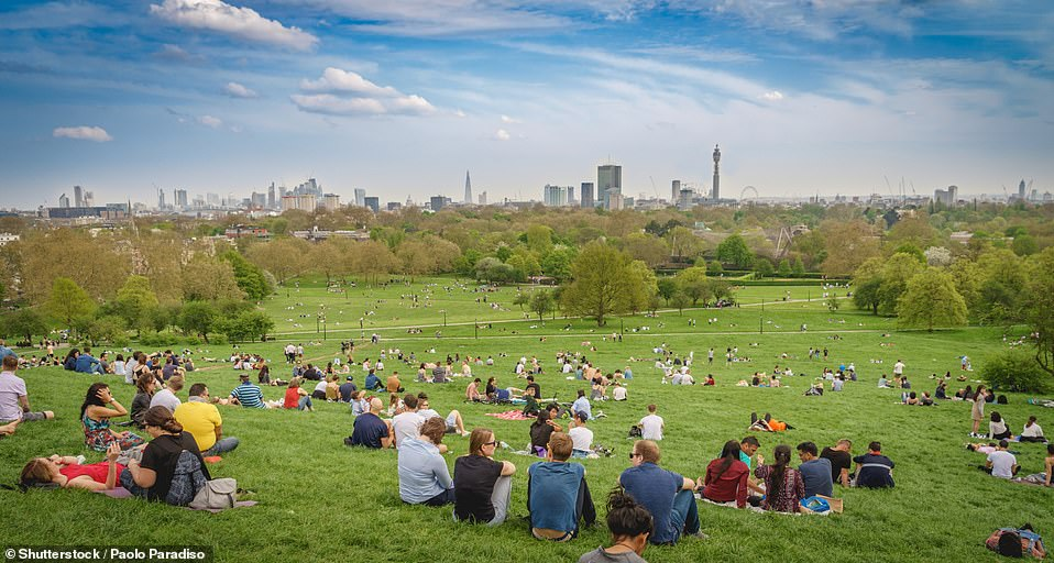 Britons can soak up the sought-after sunshine in the park with friends. Pictured: People having picnics on Primrose Hill (file image)