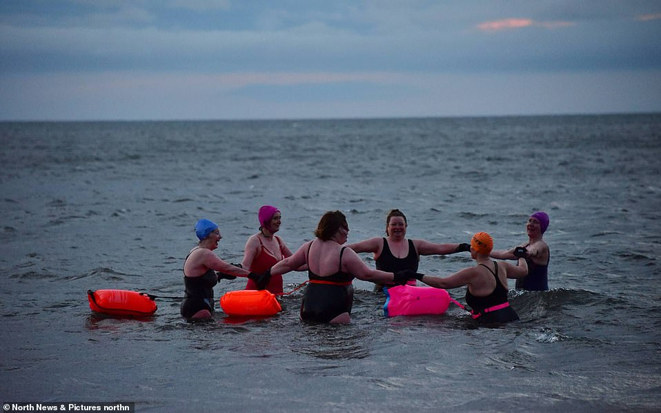 The Rule of Six comes into force today - so early morning wild swimmers take a moment to all hold hands at Seaburn beach in Sunderland at sunrise this morning
