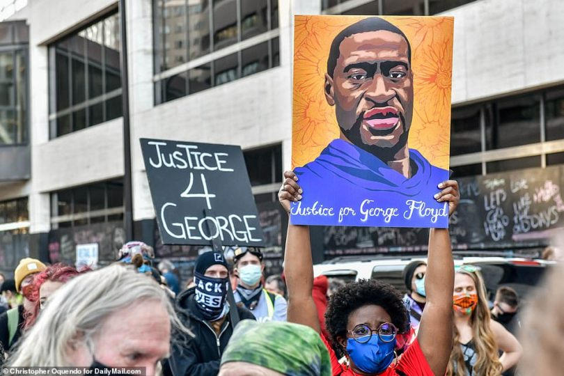 Demonstrators held up portraits of George Floyd and signs calling for 'justice for George' on Monday