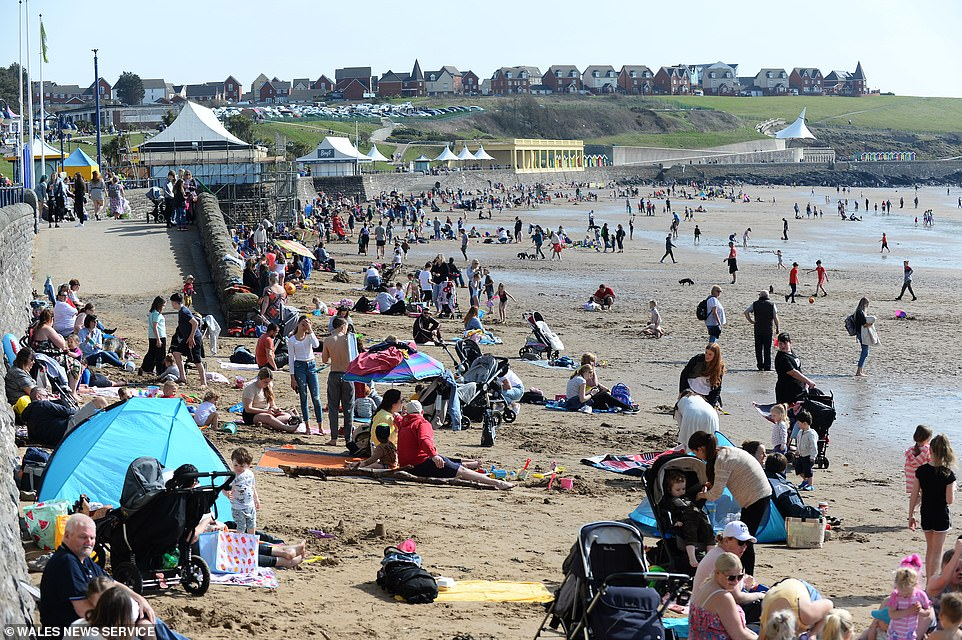 Hundreds of people flock to Barry Island beach in South Wales today as the temperatures soar in parts of Britain