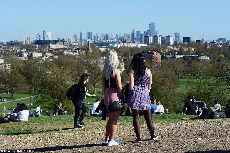 People look at the views of London from Primrose Hill today as they make the most of the warm and sunny conditions