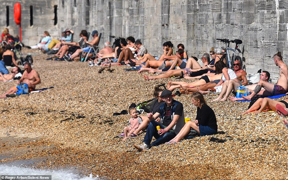 Sunseekers soak up the rays by the Hot Walls in Old Portsmouth this afternoon as temperatures soar across the South