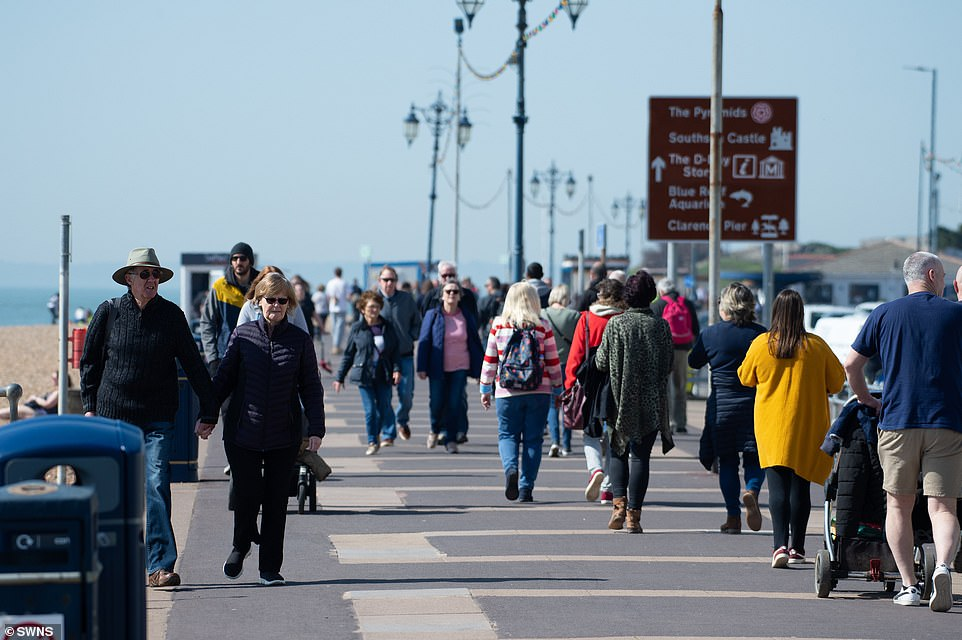People enjoying the warm weather at Southsea as they walk along the promenade in Hampshire this afternoon