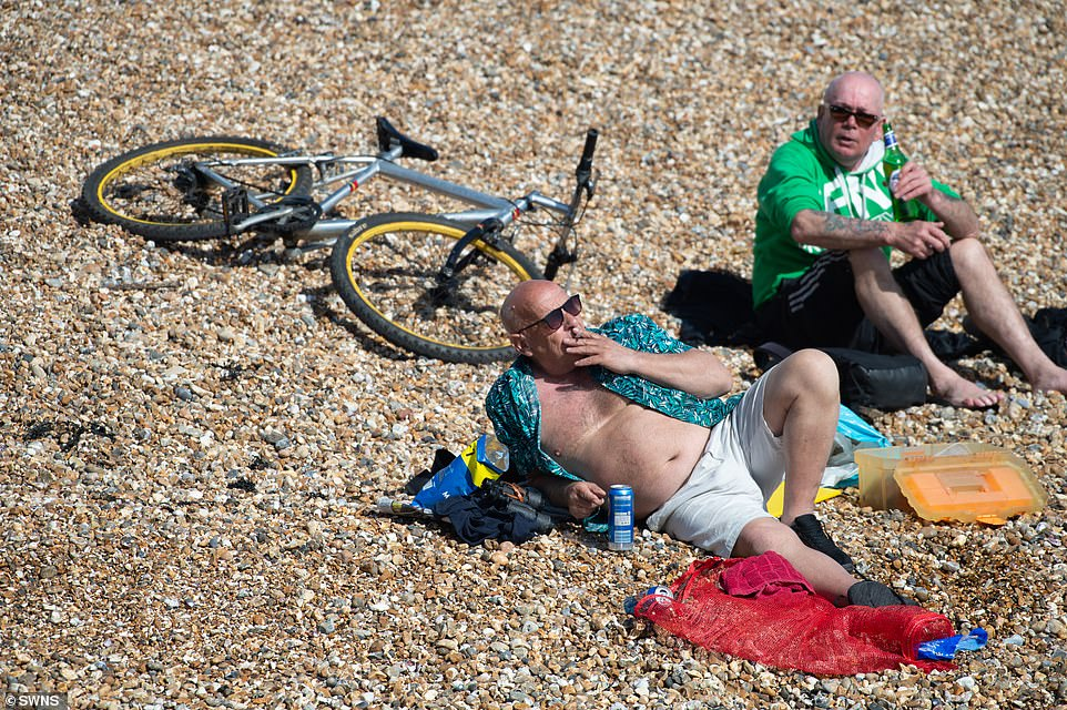 People enjoying the warm weather on the pebble beach at Southsea in Portsmouth this afternoon