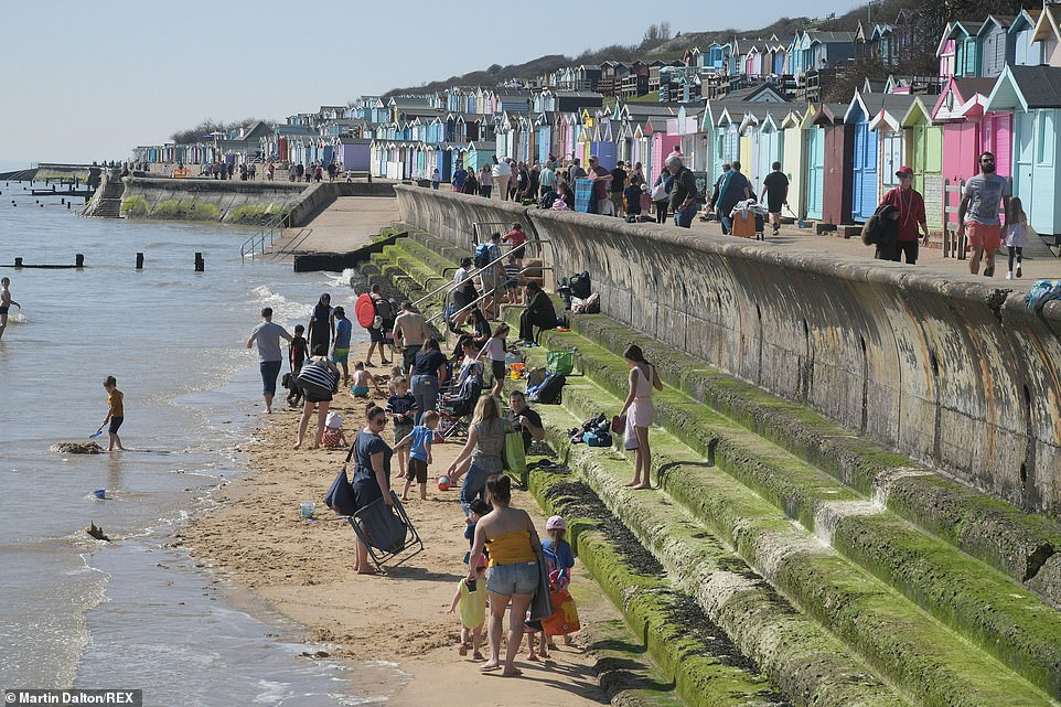 People enjoy the warm spring weather at Walton-on-the-Naze beach in Essex this afternoon