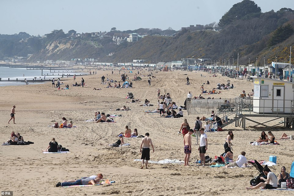 People enjoy the warm weather on Bournemouth beach in Dorset today as temperatures rise in southern England