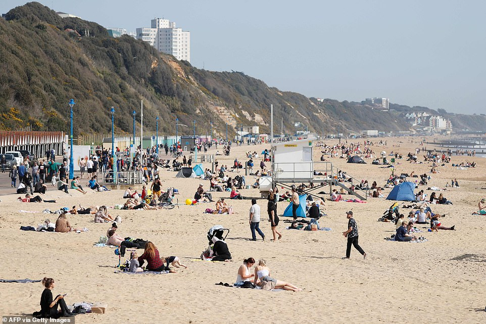 Members of the public enjoy the beach in Bournemouth in Dorset today amid a spell of warm weather in the South
