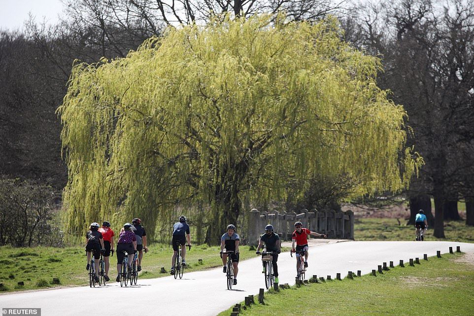 People cycle in Richmond Park today as London enjoys balmy temperatures and sunshine this afternoon