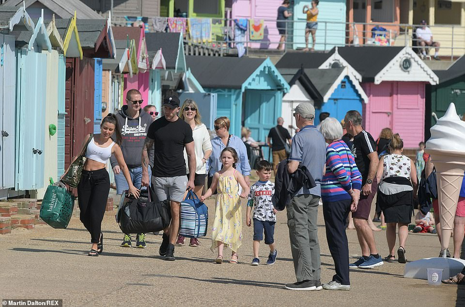 Families walk along the promenade next to Walton-on-the-Naze beach in Essex today as temperatures rise in the South