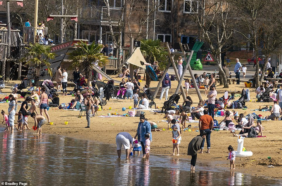 Families enjoy the warm weather at Ruislip Lido in North West London this afternoon