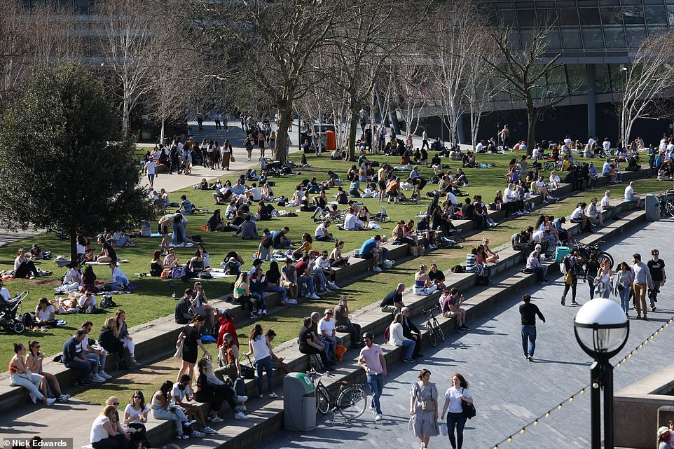 People out in the sunny weather near Tower Bridge in London this afternoon as temperatures soar into the 70Fs