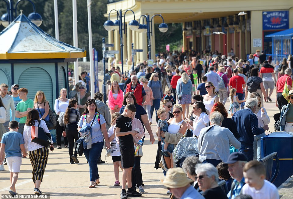 Thousands of people flock to Barry Island beach in South Wales this afternoon as the temperatures soar