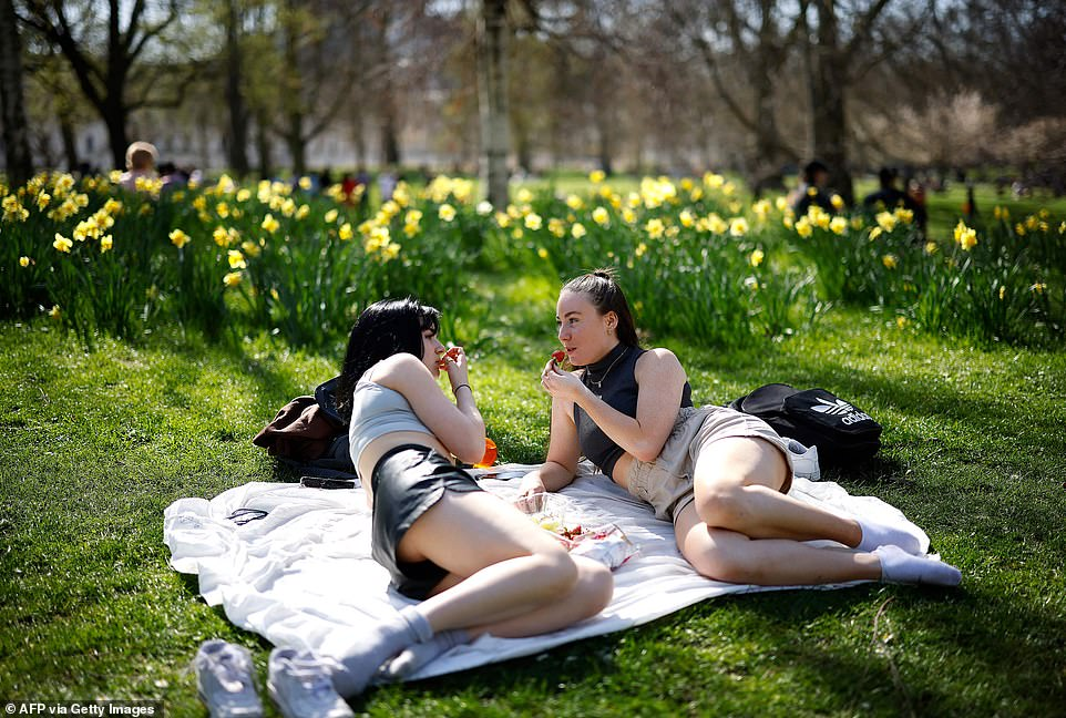 People enjoy the sunshine at St James's Park in Central London this afternoon as the hot weather continues