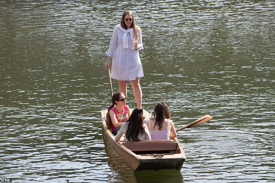 People punt along the River Cam in Cambridge this afternoon as temperatures are significantly warmer than normal