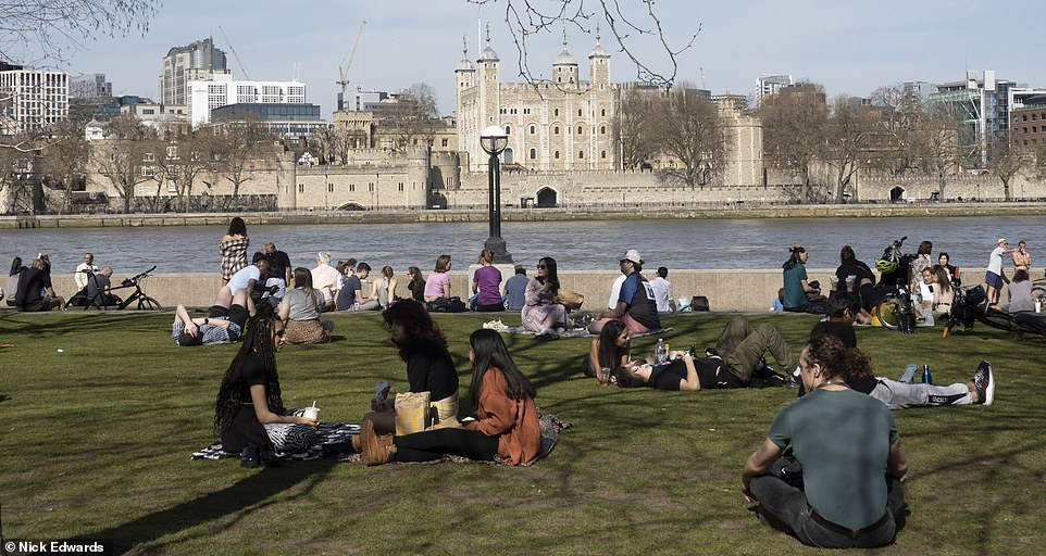 People sit on the banks of the River Thames opposite the Tower of London as they enjoy the heat today