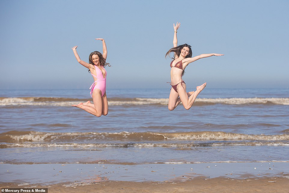 Miss England finalists Alexandra Taylor, 24, and Poppy Gerrard, 18, enjoy the heat on West Kirby Beach on the Wirral today