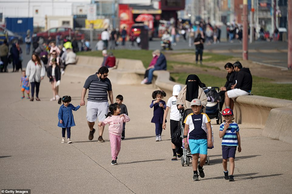 People enjoy the spring sunshine on Blackpool promenade in the Lancashire seaside resort this afternoon