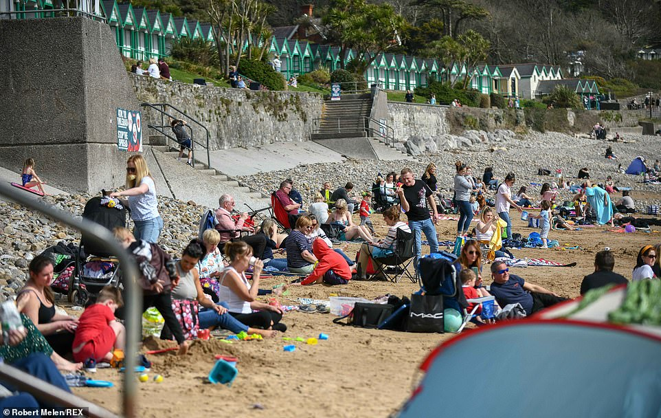 People on the sand at Langland Bay in Swansea, South Wales, on a fine spring day this afternoon