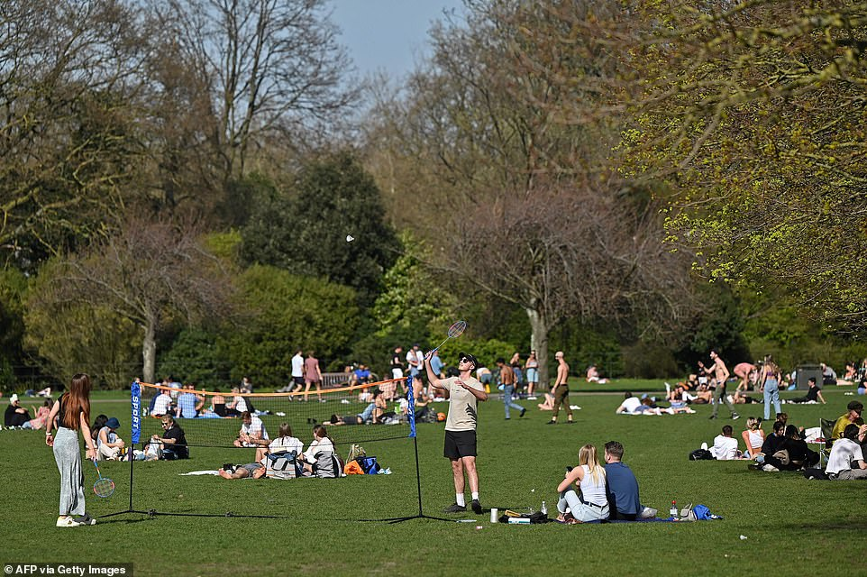 People enjoy the sunshine in Battersea Park in South West London this afternoon