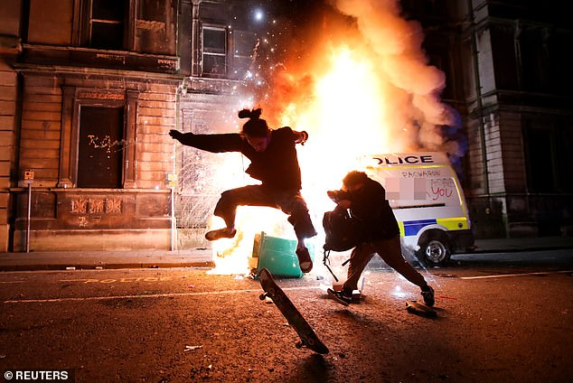 A demonstrator skateboards in front of a burning police vehicle during a protest against a new proposed policing bill, in Bristol, Sunday