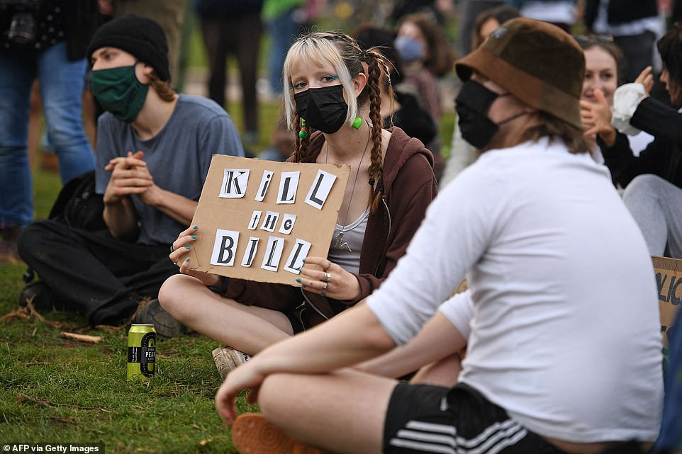 A woman with a sign reading 'Kill the Bill' is seen on sitting on the grass as demonstrations began again in Bristol