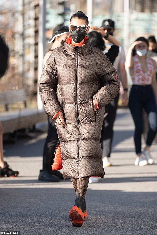 Modeling: Bella Hadid put on a very stylish display in a large brown down puffer during a photo shoot for Michael Kors by the water in Brooklyn on Tuesday afternoon