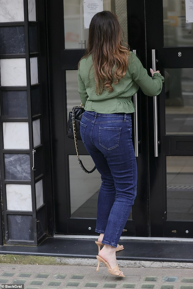 Stylish: With her glossy brunette mane loosely falling about her shoulders, Kelly carried her office fob in her hand as she strutted through the capital's streets