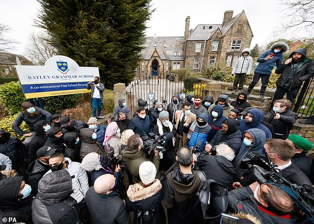 Protesters stand outside Batley Grammar School in West Yorkshire after pupils were shown a cartoon of the Prophet Muhammad