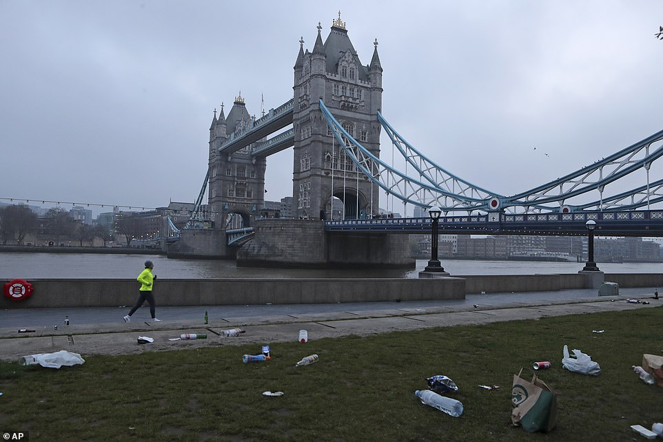 A man jogs past the litter strewn over the ground at Potters Field Park next to Tower Bridge in central London this morning
