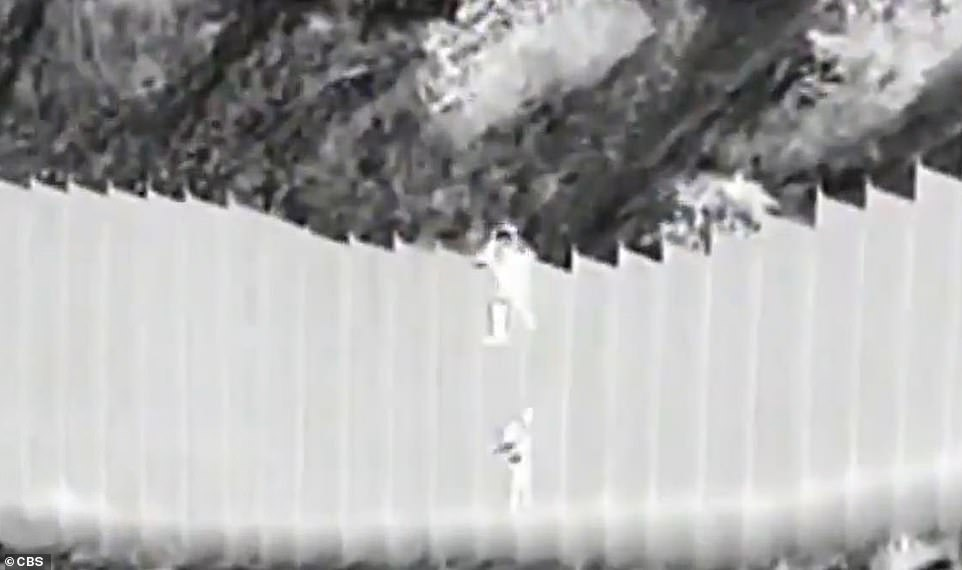Mexican smugglers have been caught on camera dropping two toddlers over a 14-foot-high border barrier into the US (pictured)