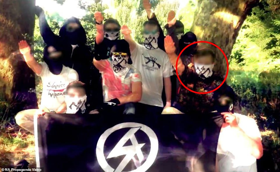 The defendant is seen doing a Nazi salute and holding a National Action flag during a meeting of the neo-Nazi group