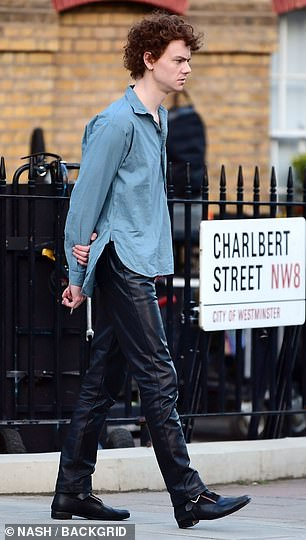 Details: He teamed it with black leather-look trousers with pointed boots