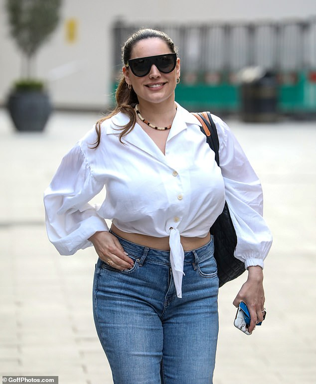 Sensational:Kelly highlighted her famous curves in the white shirt which she had knotted at the front to present her show on Heart