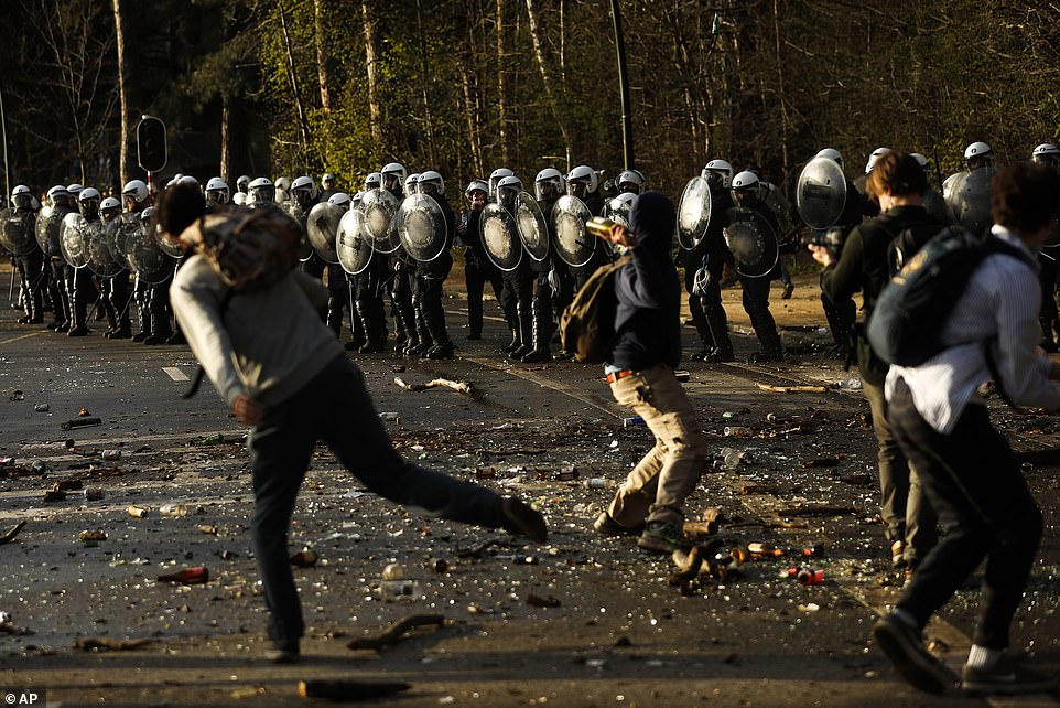 People throw stones and bottles towards the police during a protest at Bois de la Cambre park in Brussels