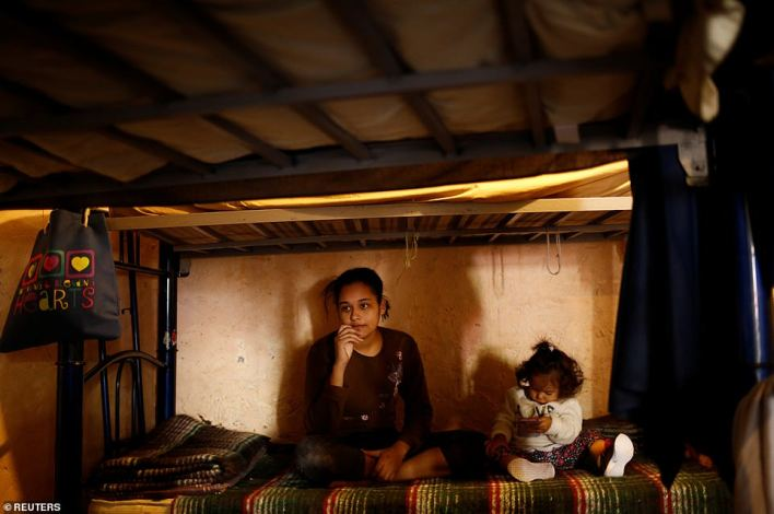 Sandra Soto an asylum-seeking migrant from Honduras, sits with her daughter inside the hostel in Mexico on Thursday, having been deported to Mexico