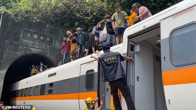 Passengers are seen escaping over the roof of the train which was crowded with tourists for the weekend