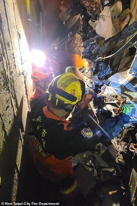 Rescuers try to cut their way inside a mangled carriage