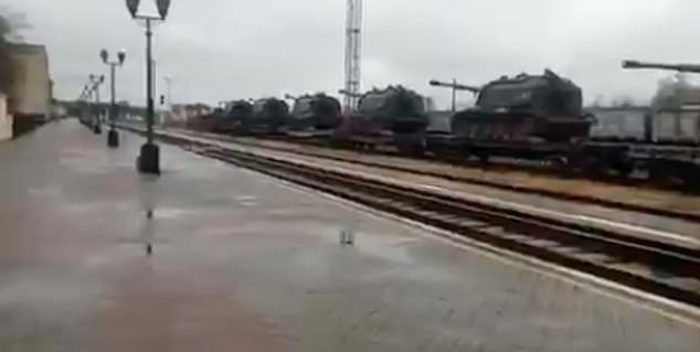 Tanks are transported by freight train at a station headed towards the separatist region on the border with Ukraine