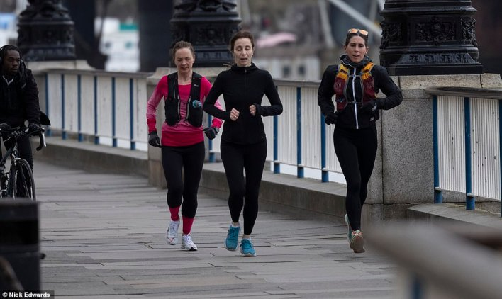 People out for a morning jog on London's south bank this morning at the start of the four-day Easter weekend